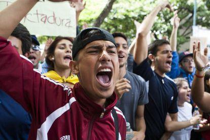 Jóvenes venezolanos gritan consignas frente a la Comisión Nacional de Telecomunicaciones.