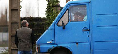 Un hombre espera a una prostituta frente a un vehículo.