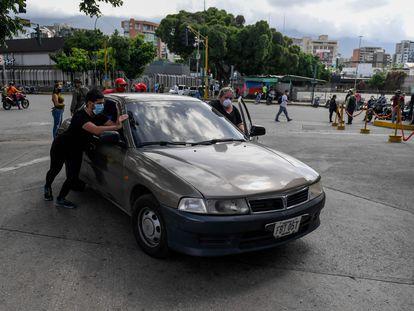Varias personas empujan un coche para cargar gasolina en Caracas (Venezuela), este lunes.