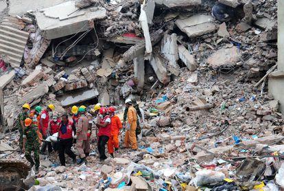 Varios miembros del personal de emergencias rescata el cadáver de una persona entre los escombros del edificio Rana Plaza de Dacca, en Bangladés, donde se ubicaban varias fábricas textiles, en abril de 2013. El derrumbe provocó más de mil muertos.