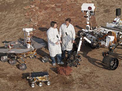 Dos ingenieros, junto a modelos de 'Sojourner' (en el frente),  'Spirit' y 'Opportunity' (izquierda) y 'Curiosity' (derecha).