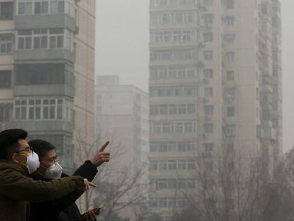 Dos hombres se protegen de la polución en Pekin con mascarillas.