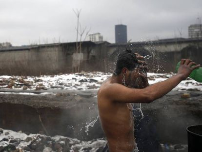 Un hombre se lava en un aseo improvisado a las afueras de Belgrado (Serbia).