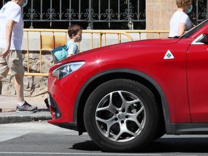 Un niño pasa ante un vehículo tipo SUV.