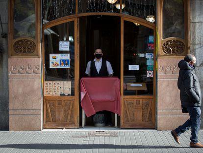 En la imagen, un camarero en la Rambla de Barcelona espera desde la puerta del establecimiento la llegada de algún cliente.