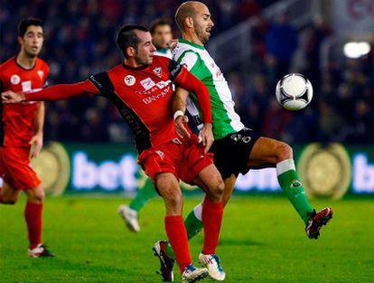 El delantero del Mirandés, Alain (i), trata de alcanzar un balón ante el centrocampista del Racing de Santander, Gonzalo Colsa.