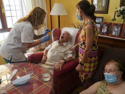María Bermúdez hace el test a Luis, de 88 años, en su domicilio en presencia de su esposa y su hija.