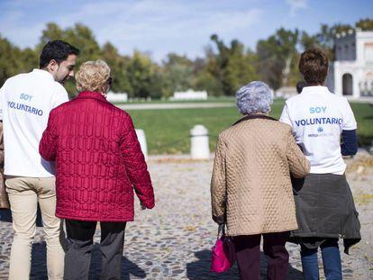 Dos voluntarios caminan junto a dos mujeres.