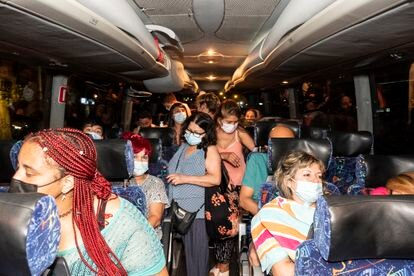 Pasajeros del Bus Playero Viajero con destino Benidorm durante la recogida de pasajeros en Madrid, la madrugada del sábado.