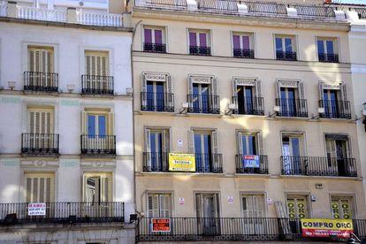 Fachada de un edificio de Madrid con diferentes carteles de venta y alquiler de pisos.