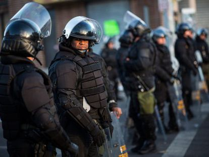 Un grupo de antidistubios estaciona ante una farmacia incendiada en los disturbios del lunes en Baltimore.