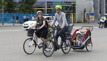 Unos padres en bicicleta con sus hijos pequeños.