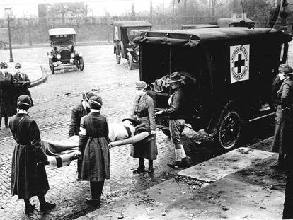 Miembros de la Cruz Roja llevan a un enfermo de gripe española, en Saint Louis, Missouri (EE UU), en octubre de 1918.