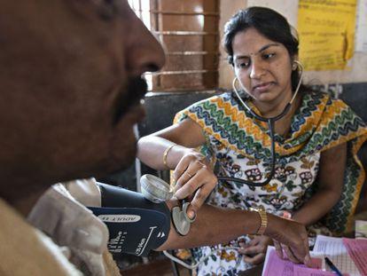 La estudiante de medicina Prathyusha toma la tensión a un paciente.