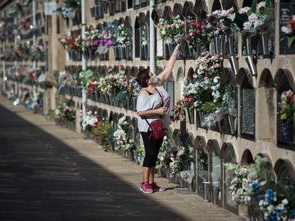 Una mujer deposita flores en un nicho del cementerio del Poblenou