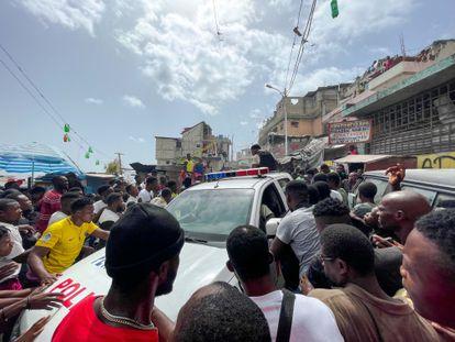 Decenas de personas se aglomeran en torno a un automóvil de la Policía en el que hay dos colombianos capturados por un grupo de personas en Puerto Principe (Haití).
