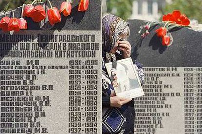 Una viuda llora a su marido ante el monumento erigido en Kiev en memoria de los fallecidos por el accidente nuclear de Chernóbil.