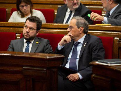 El vicepresidente y el presidente de la Generalitat, Pere Aragonès y Quim Torra, sentados en sus escaños en el Parlament. En vídeo, la portavoz de JxCat, Laura Borràs, en una rueda de prensa.