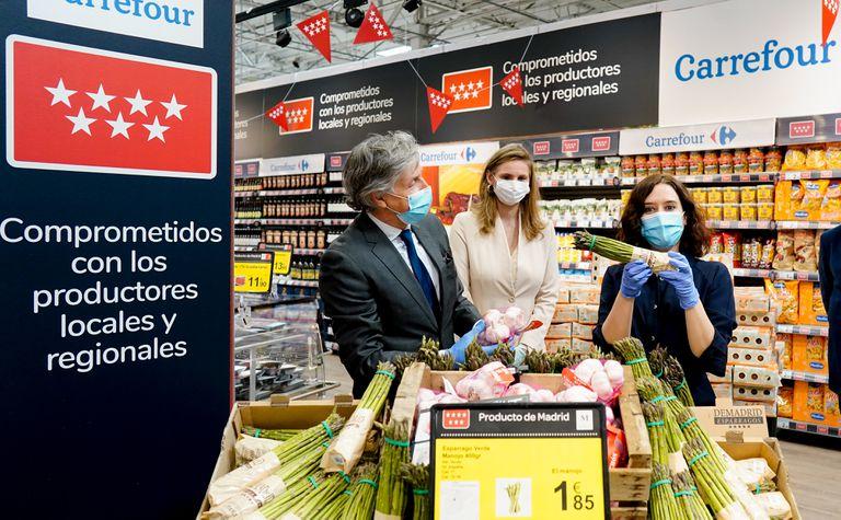 La presidenta de la Comunidad de Madrid, Isabel Díaz Ayuso, sostiene un manojo de espárragos del Carrefour de Alcobendas.