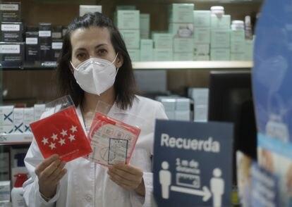 Una farmacéutica muestra una mascarilla del Gobierno regional en una farmacia de la capital.