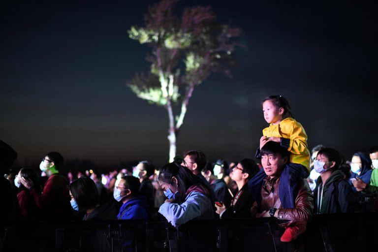 Un hombre sostiene a una niña durante un concierto celebrado bajo el cielo de Pekín el pasado lunes.