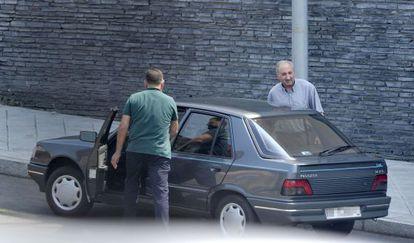 El exjefe de la Policía de Ourense, Abelardo Ulloa (de frente) junto al coche con el agente que usa de chófer particular.