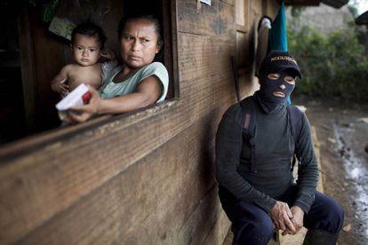 Un miembro del cuerpo de autodefensa de la comunidad indígena shuar descansa junto a una vivienda en Yunkuapais, a finales de enero.