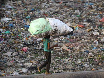 Un hombre transporta una bolsa llena de plástico reciclable cerca en Nueva Delhi el pasado mayo.