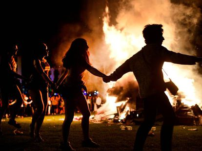 People dance around a bonfire on San Juan's Night in Mundaka, Spain, June 24, 2018. Fires are lit throughout Spain on the eve of Saint John, where people burn objects they no longer want and make wishes as they jump through flames. REUTERS/Vincent West