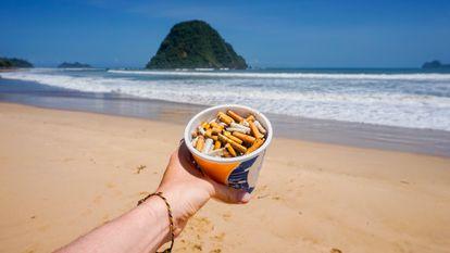 Un vaso de plástico reutilizado como cenicero en la playa.
