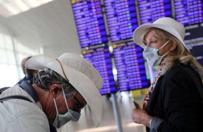 Dos viajeros con mascarillas esperan su vuelo en el aeropuerto de El Prat.