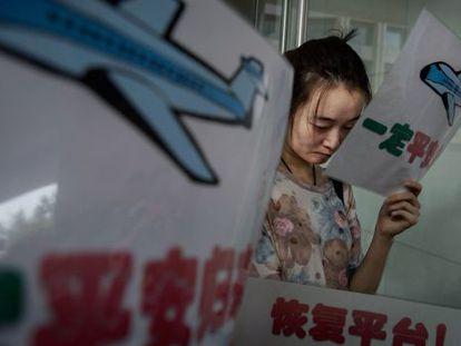 La familiar de una víctima del MH370 aguarda para obtener información en las oficinas de Malaysia Airlines en Pekín.