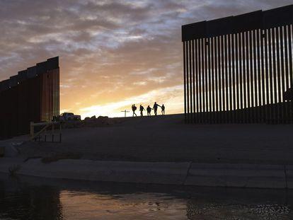 Familias de migrantes cruzan el muro fronterizo entre México y Estados Unidos.
