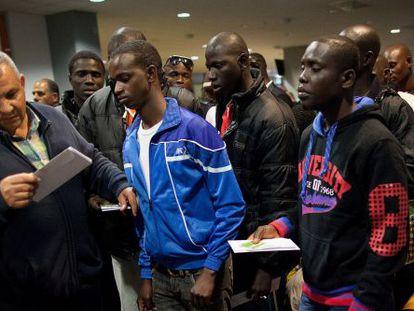 Unos inmigrantes se disponen a embarcar en Melialla rumbo a Málaga.