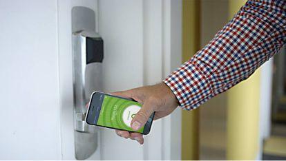 Un usuario abre la puerta de su hotel con una llave digital.