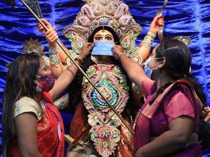 Dos mujeres le colocan una mascarilla a una imagen de la diosa hindú Durga, en Calcuta, el pasado mes de octubre.