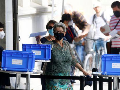 Una mujer deposita su voto para el referéndum este domingo en una mesa de votación en Zúrich.