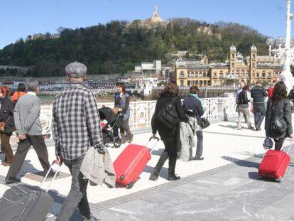 Varios turistas, en el paseo de La Concha en San Sebastián.