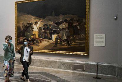 Dos visitantes del Prado pasan delante de 'Los fusilamientos' de Goya.