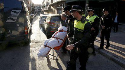 Agentes de la Policía Municipal y empleados de los servicios funerarios trasladan el cadáver de la mujer degollada en Puente de Vallecas.