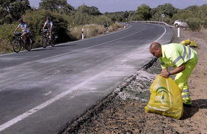Un empleado de conservación de carreteras limpia los últimos restos del lugar del accidente de Ortega Cano.