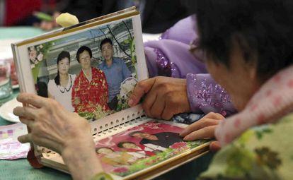 Una familia observa una fotografías durante el reencuentro de parientes de Corea del Norte y Corea del Sur.