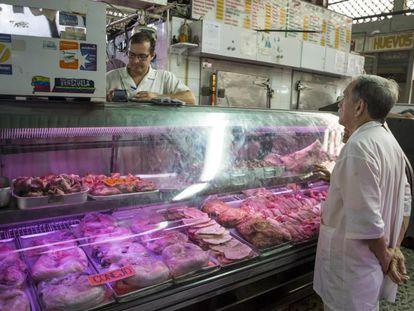 Un hombre pregunta el jueves el precio de la carne en un mercado popular de Caracas.