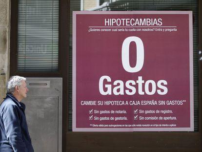 Un hombre pasa ante un anuncio de hipotecas en una sucursal bancaria en Madrid.