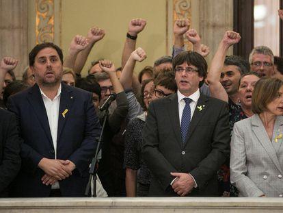 En el centro de la imagen, el expresidente de la Generalitat, Carles Puigdemont, entre el exvicepresidente, Oriol Junqueras, y la expresidenta del Parlament, Carme Forcadell, tras aprobarse la declaración de independencia, en octubre de 2017.