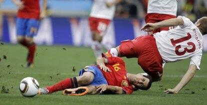 Sergio Busquetsy el Stephane Grichting, por los suelos tras un lance en el juego.