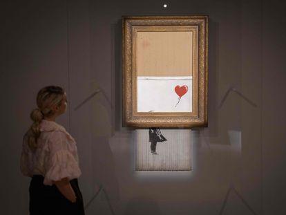 'El amor está en la papelera', una de las obras más famosas del artista británico Banksy, fotografiada en la casa de subastas Sotheby's en el centro de Londres el 8 de octubre de 2021.