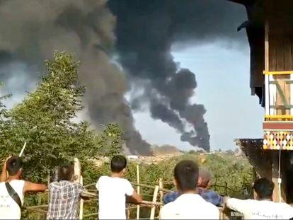 Varias personas observan columnas de humo en Hkamti, en la región birmana de Sagaing, en una imagen difundida este sábado en las redes sociales.