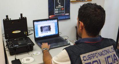 Fotografía facilitada por la Policía Nacional de un agente que analiza material informático de la operación.