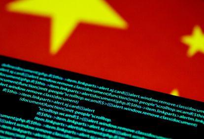 Código de ordenador en una pantalla junto a una bandera de China